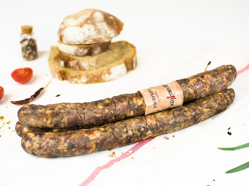 кухненска кърпа с две цели парчета кървавица, домати, сушени люти чушки и домашен хляб на заден план