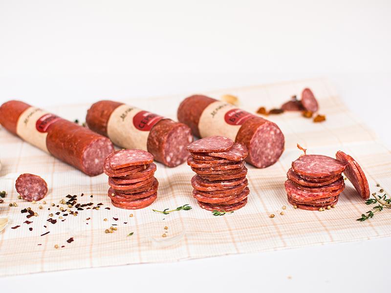 домашна покривка на каре и три броя шпеков салам нарязани до половината, резените са на купчина пред колбаса, готови за хапване