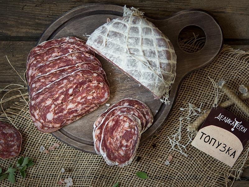 дъврена кръгла дъска с разрязана на половина Топузка и резени от един от малкото качествени български колбаси